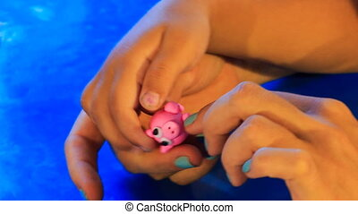 kid's and mother's hands sculpture pink toy animal of...