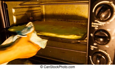 woman in gloves takes tray with cake out of oven - womans...