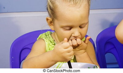 closeup little blonde girl eats soup out of bowl