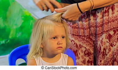 closeup mother braids little blonde daughter's plait girl...