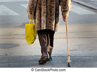 woman with shopping bag and walking stick