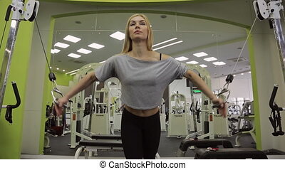 A blonde woman athlete, doing exercise on the chest and front delts shoulder in the gym