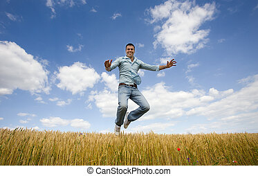 Happy man jumping - Young attractive man jumping over yellow...