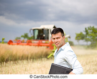 Farmer with laptop in the field - Young attractive farmer...