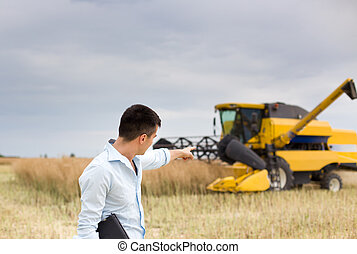 Businessman with combine harvester - Young businessman...