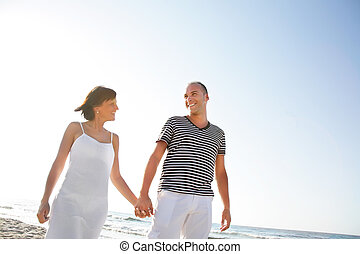 Happy young couple taking a walk on the beach.
