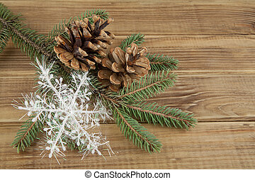 branch of Christmas tree, pine cones and snowflake on wooden...