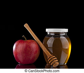 apple and honey on a black background