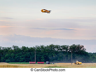 Rural landscape of tractor and combine harvester working in...