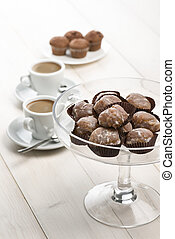 marron glace on glass tray on white table with cups of...