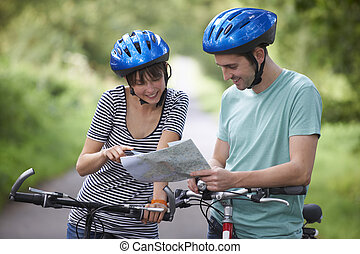 Young Couple Looking At Map Whilst On Cycle Ride