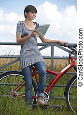 Young Woman Looking At Map During Cycle Ride