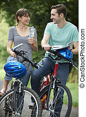 Young Couple Having Break Whilst On Country Cycle Ride