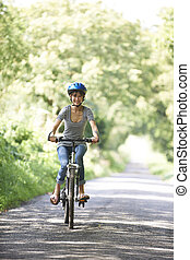 Young Woman Enjoying Cycle Ride In Countryside