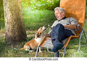 Senior man with dog - Senior man sitting in sunbed in park...