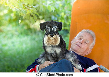 Senior man with dog - Senior man lying in sunbed in...