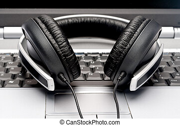 Horizontal image of silver colored headphones on a notebook...
