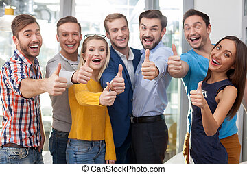 Cheerful young office workers are gesturing positively -...