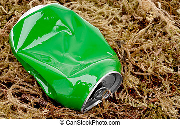 horizontal close up of a crushed green aluminum drink can on moss