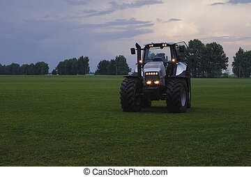 tractor with head lights in field at dusk - agro tractor...