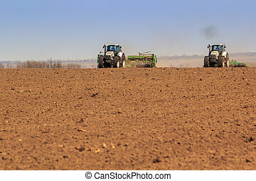 panorama of two tractors sowing in field - panorama of two...
