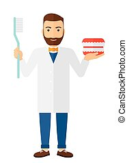 Dentist with dental jaw model and toothbrush. - Dentist with...
