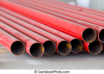 Red metal pipes - Close up of red metal pipes stacked on...
