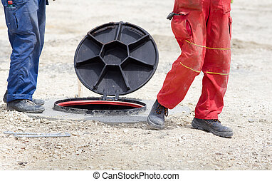 Workers beside manhole - Construction workers standing...