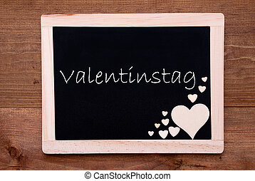 Blackboard With Wooden Hearts, Text Valentinstag Means...