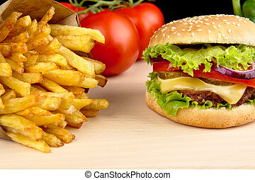 Cheeseburger,french fries with in the bar on wooden desk on black
