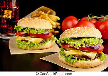 Cheeseburgers,french fries on wooden desk on black