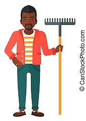 Man standing with rake. - An african-american man standing...