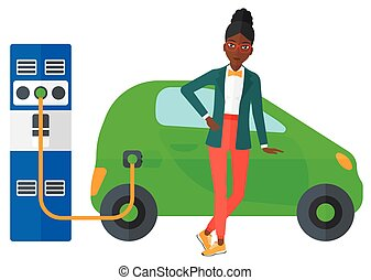 Charging of electric car - An african-american woman...