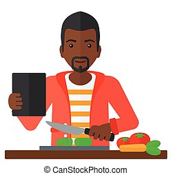 Man cooking meal. - An african-american man holding a...
