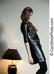 Young seductive woman in a black leather dress
