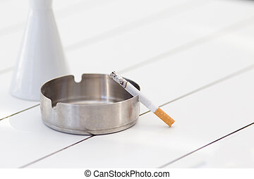 Cigarette in ashtray on the table - Burning cigarette in...