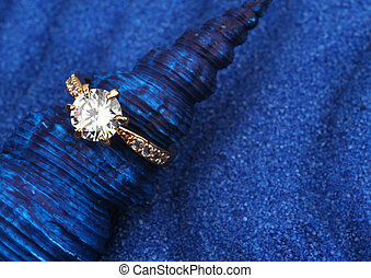 macro photo of jewelry ring with big diamond on blue seashell and sand background