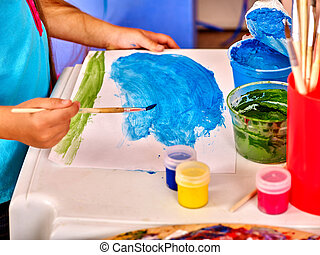 Child hands with brush painting on table in kindergarten . -...