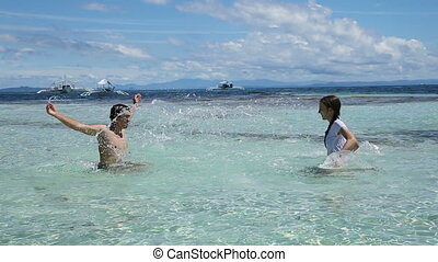 man and his daughter splashing water in the sea.