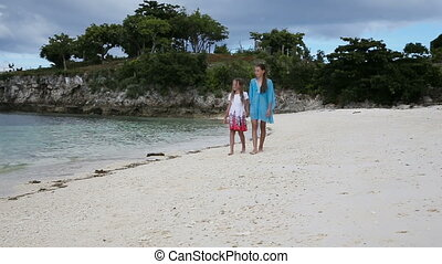 Two girls walking on a tropical beach - Happy sisters having...