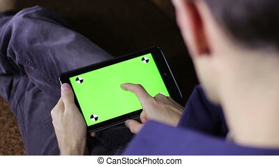Man Using Tablet Computer on the Couch with Green Screen -...