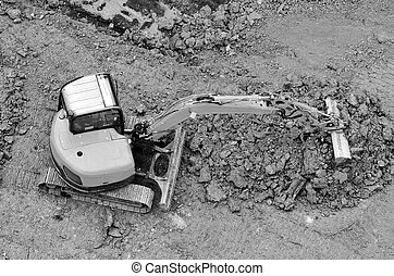 Excavator digs soil in a construction site. Industrial...