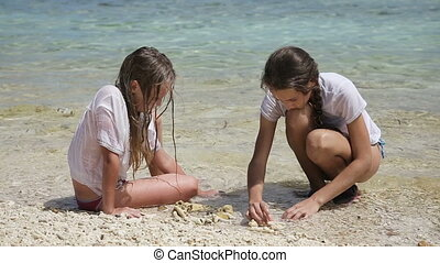 Happy girls playing with sand on beach in summer - Young...