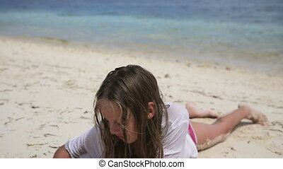 Happy child playing with sand on beach in summer - Young...