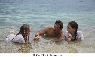 Father with daughters in the tropical sea