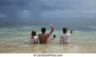 Father with daughters throw pebbles into the sea.