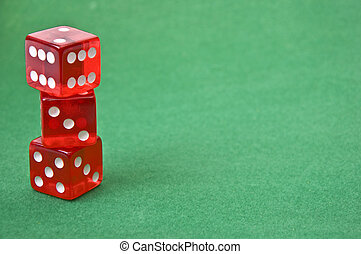 dice against green baize - set of three red dice against...