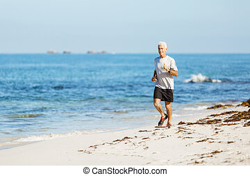 Healthy running man on beach