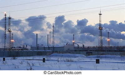 Refinery at sunset sky background. Frosty snowy winter...