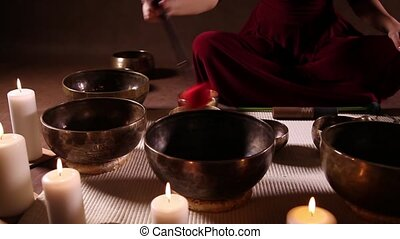 Woman playing Tibetan bowls close-up - Dolly video shot of...